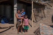 Mirna and her children in front of her dreary shack