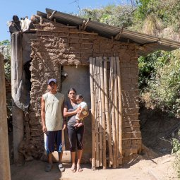 The Calles family outside their old home