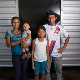 Juan Pablo and Zulma in front of their new house with their children, Yeslin and Naun